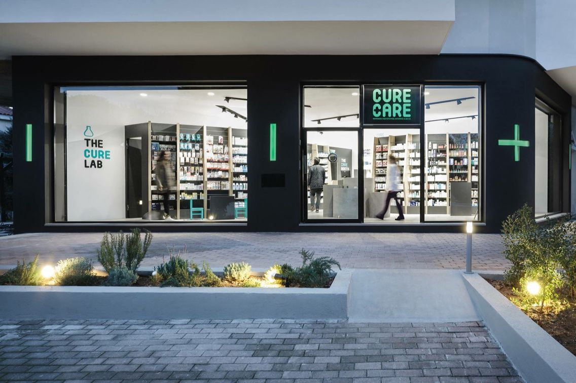 Cure and care pharmacy shop athens pharmacy design for Retail exterior design