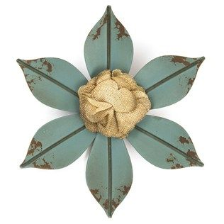"""Tip toe through the tulips. Create a wonderful wonderland of floral proportions with Blue Metal Flower with Burlap Center. This lovely flower features 6 petals with a slight distressed appearance at the tip and a layered burlap flower in the center. Turn your home or office into a garden of delight.    Dimensions:      Width: 10""""      Hanging Hardware: 1 keyhole hanger"""