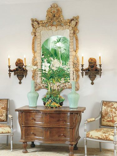 Gorgeous vignette. Charles Faudree. Love the mirror with shells, blackamoor sconces, chairs with tropical upholstery, antique commode