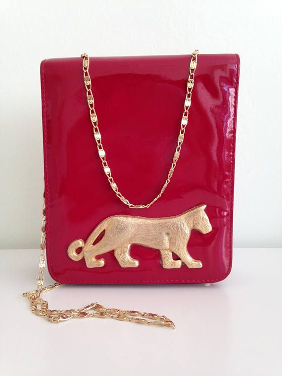 Cute patent leather shoulder purse in bright red color with elegant gold chain strap. This pretty evening structured purse is perfect for any special occasion or evening party. It will surely get all eyes on you. With the adorable gold tone cat figure on the front of this evening clutch, you will feel like a real tigress, ready to catch your pray. This boxy purse is made of genuine leather. It is by the brand Dowli and it was made in the USA in the 80s. It opens with a magnetic closure. The…