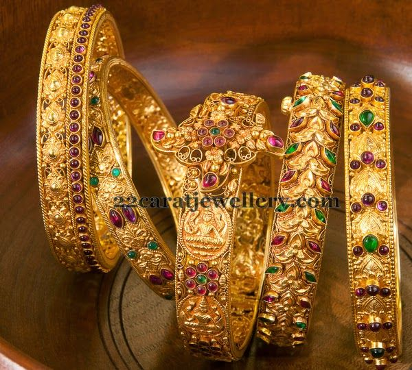 1fd6a9f70e2 Antique work broad gold bangles with floral clasps and lakshmi embossed all  over. Semi precious gemstones studded all over.