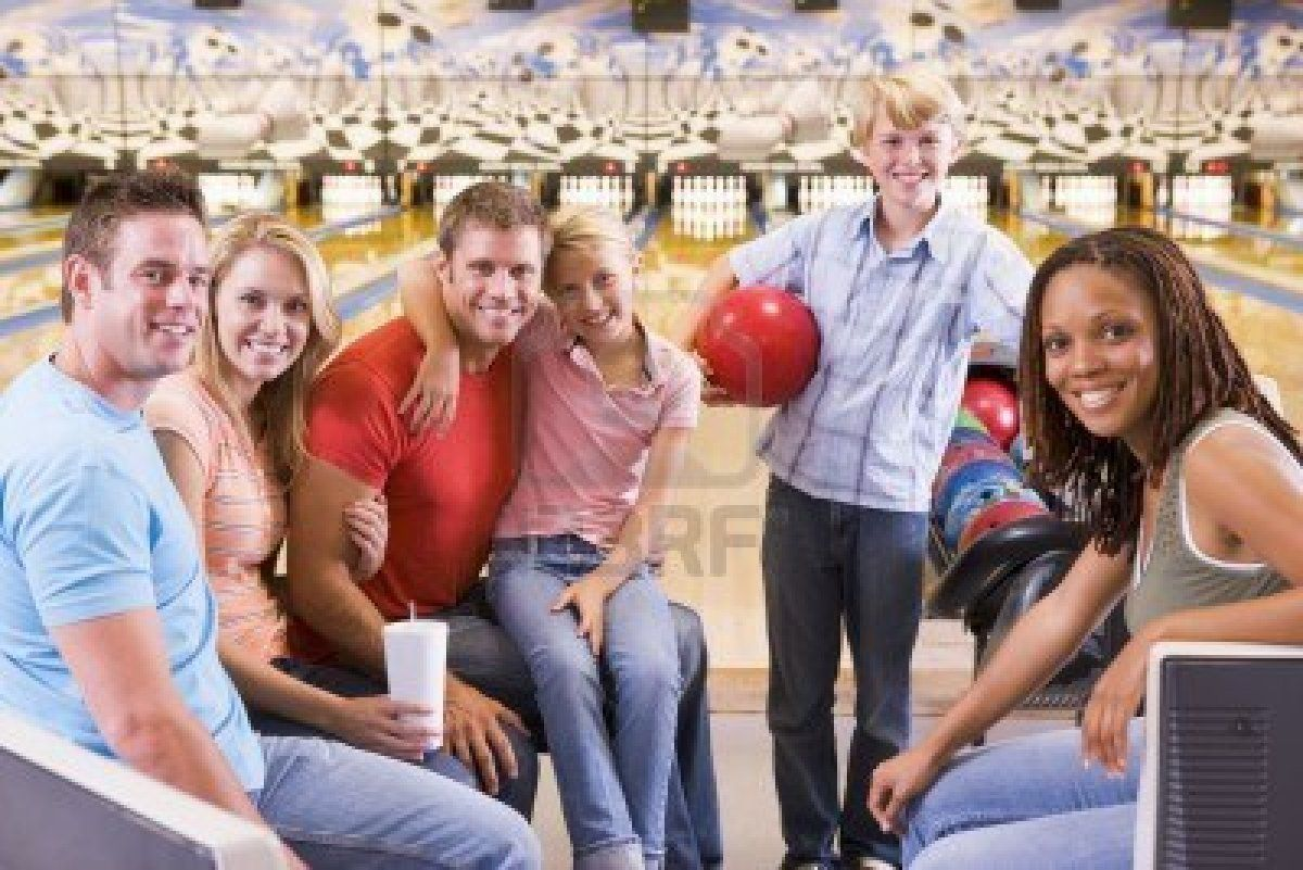 Family In Bowling Alley With Two Friends Smiling Family