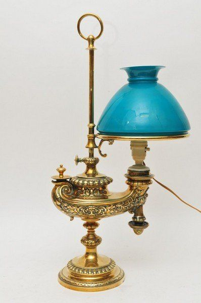 A Victorian brass oil lamp in the form of an ornate Roman style oil lamp with green glass shade and later electric conversion, Patent Wild &...
