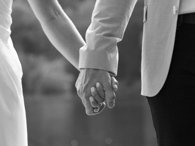 Ehepaar hält sich an den Händen.