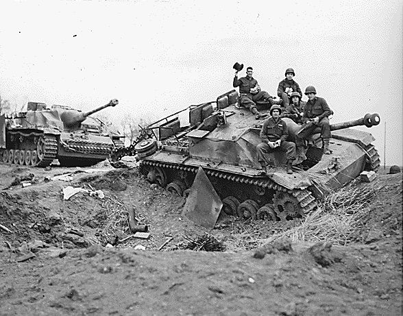 American troops posing atop one of two knocked-out StuG III Ausf G assault guns near Modrath, Germany, 1945; the vehicles were disabled by U...
