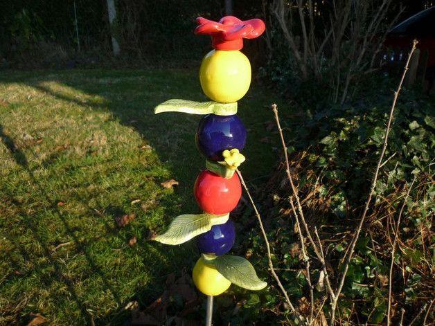 Eine verspielte, farbintensive Stele mit 5 Kugeln in den Farben gelb, blau und rot, 3 Blätter, 1 gelbes Blümchen und 1 rote Blume zum Aufstecken!  Die Keramikelemente werden auf eine Gewindestange...