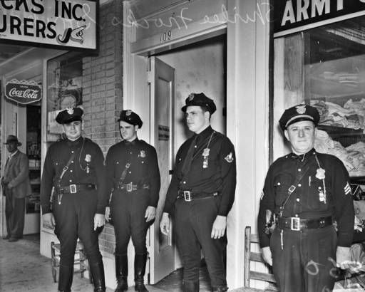 Police stand on a downtown sidewalk after removing pickets