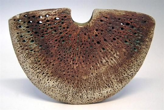 Alan Wallwork vase of crescent shape with punctured glazed faces, with cut through incised AW to