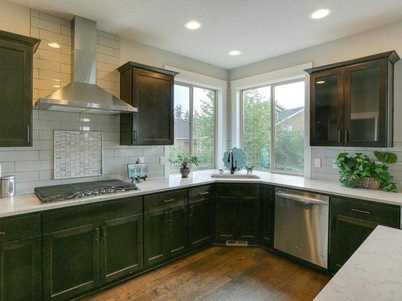 Kitchen With Shaker Style Espresso Stained Maple Cabinetry Stainless Steel Hood Vent And
