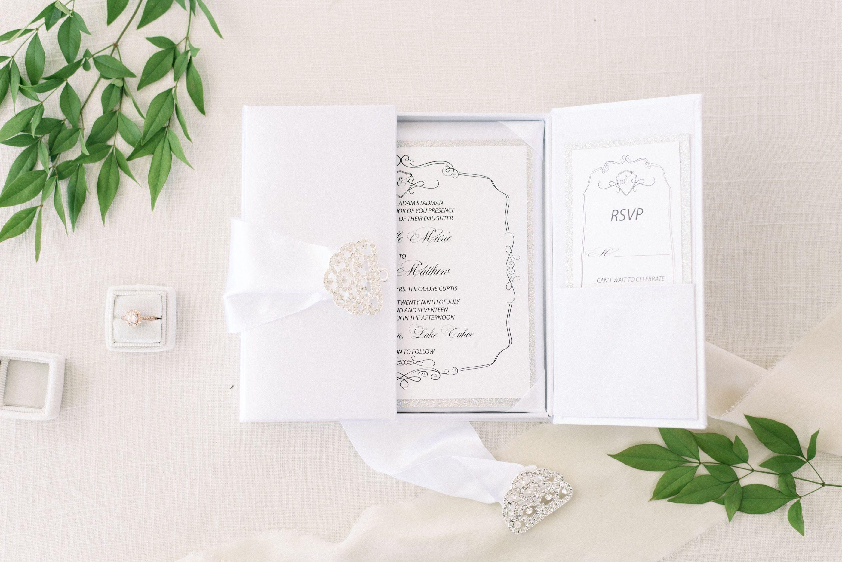Beautiful white silk invitation box adorned with a satin ribbon and ...