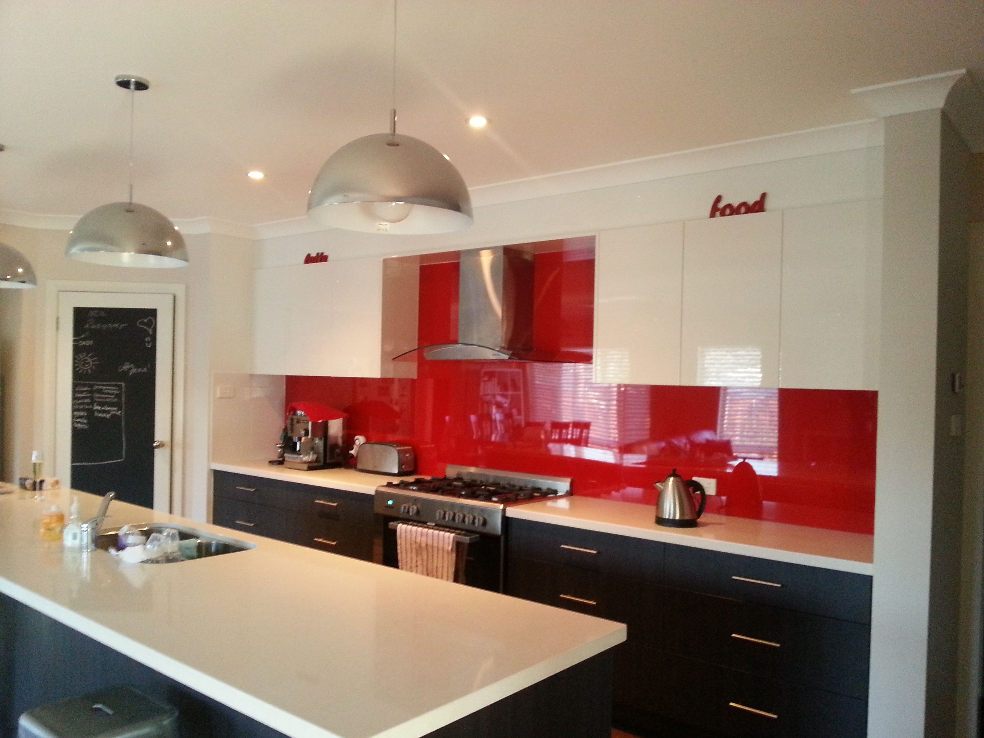 red kitchen splashback dark cupboards under light cupboards over white bench top - Red Kitchen Ideas