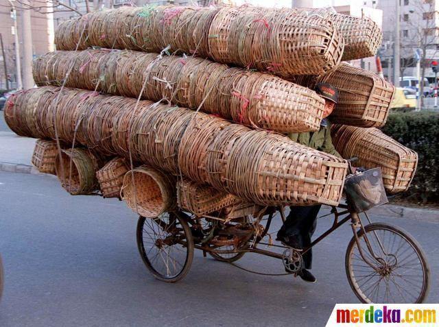 Seorang pria mengangkut keranjang bambu menggunakan sepeda di sebuah jalan di Beijing Cina.