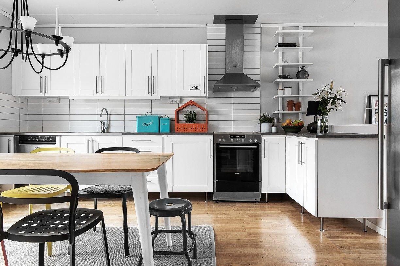 Kök med vita lådor och skåpsluckor, vitt kakel, mörkare bänkskiva ...