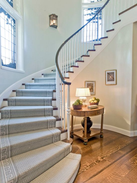 Elegant Staircase In Curvy Line Design Featured With Patterned Grey Carpet Covering Wooden Steps And Sleek Railing