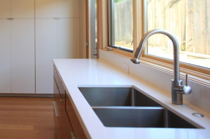 Modern kitchen; lots of natural light, white counter tops, wood floor, stainless steel sink and faucet, white cabinets