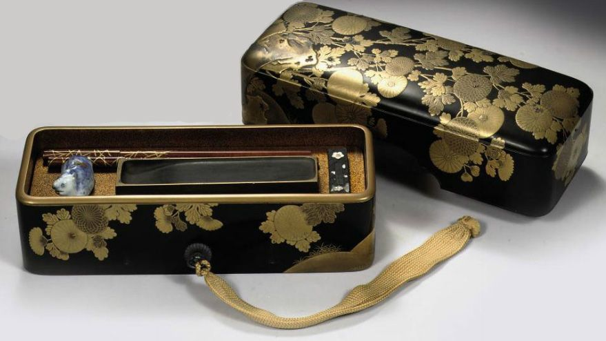 Suzuribako 19th Century. Interior fitted with tray fitted with an inkstone and a porcelain water-dropper, also including two brushes and an ink-cake. 24.2 cm. wide, wood box and silk cover.