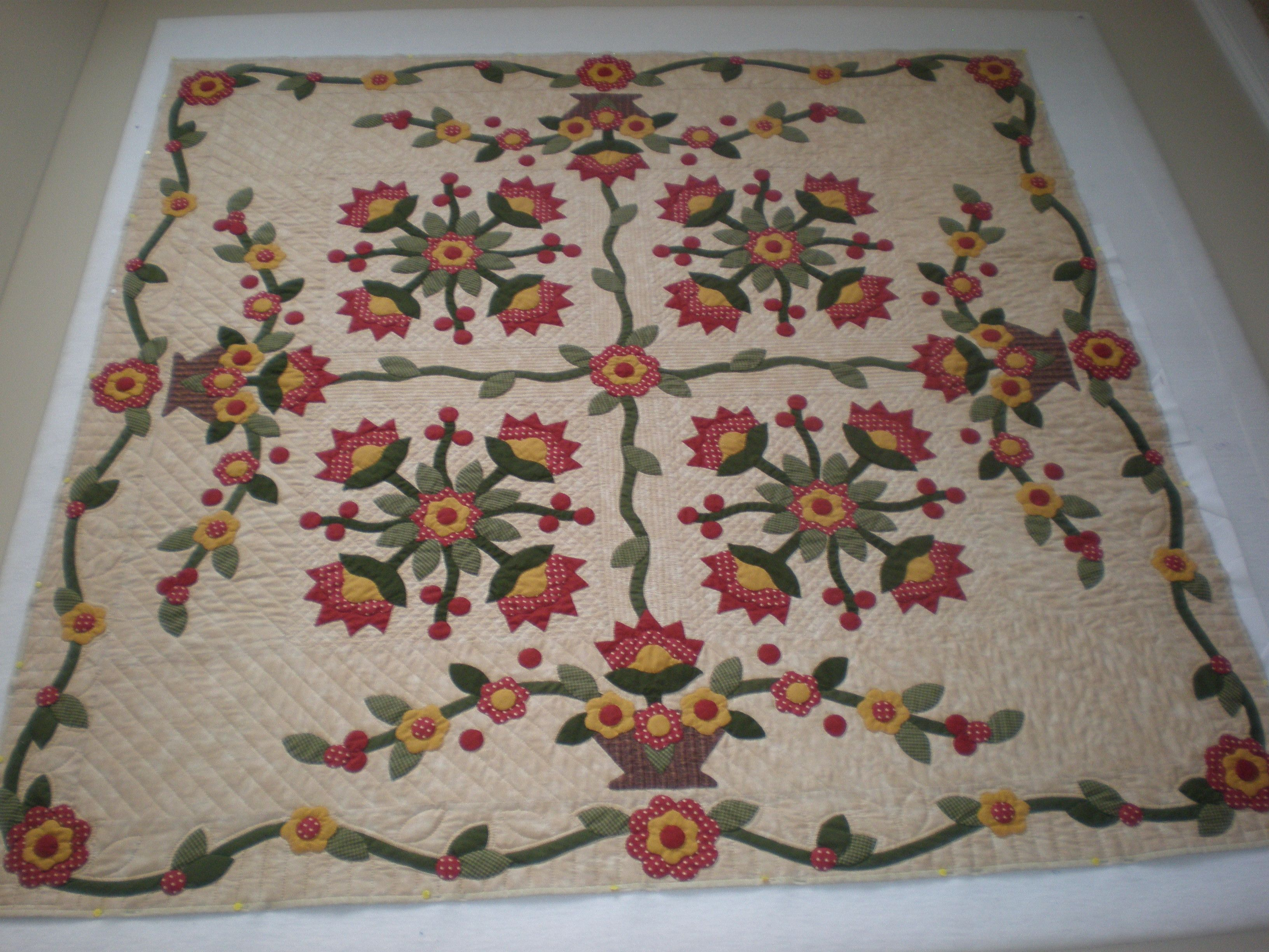 """1860's inspired red and green """"Coxcomb & Currents"""" quilt."""