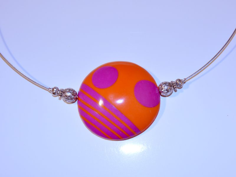 Orange a fucshia coloured hollow bead strung on 1 mm silver coloured tiger tail.