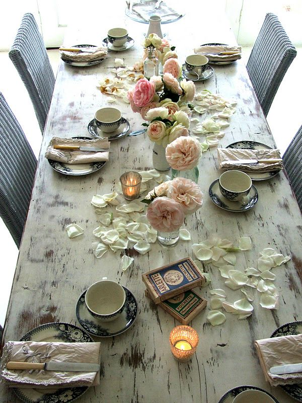 Antique china and roses on the rustic farm table