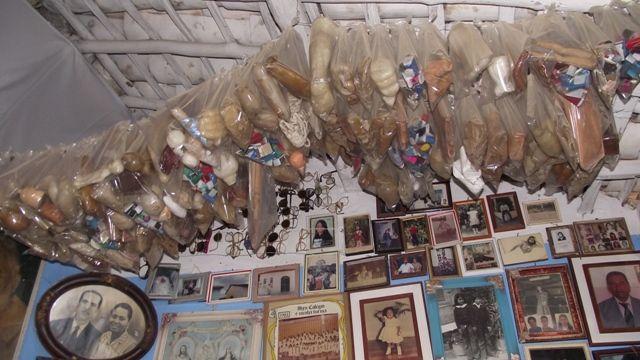Teto da casa com objetos ex-votivos, parede com quadros emoldurados de pessoas que receberam graças.