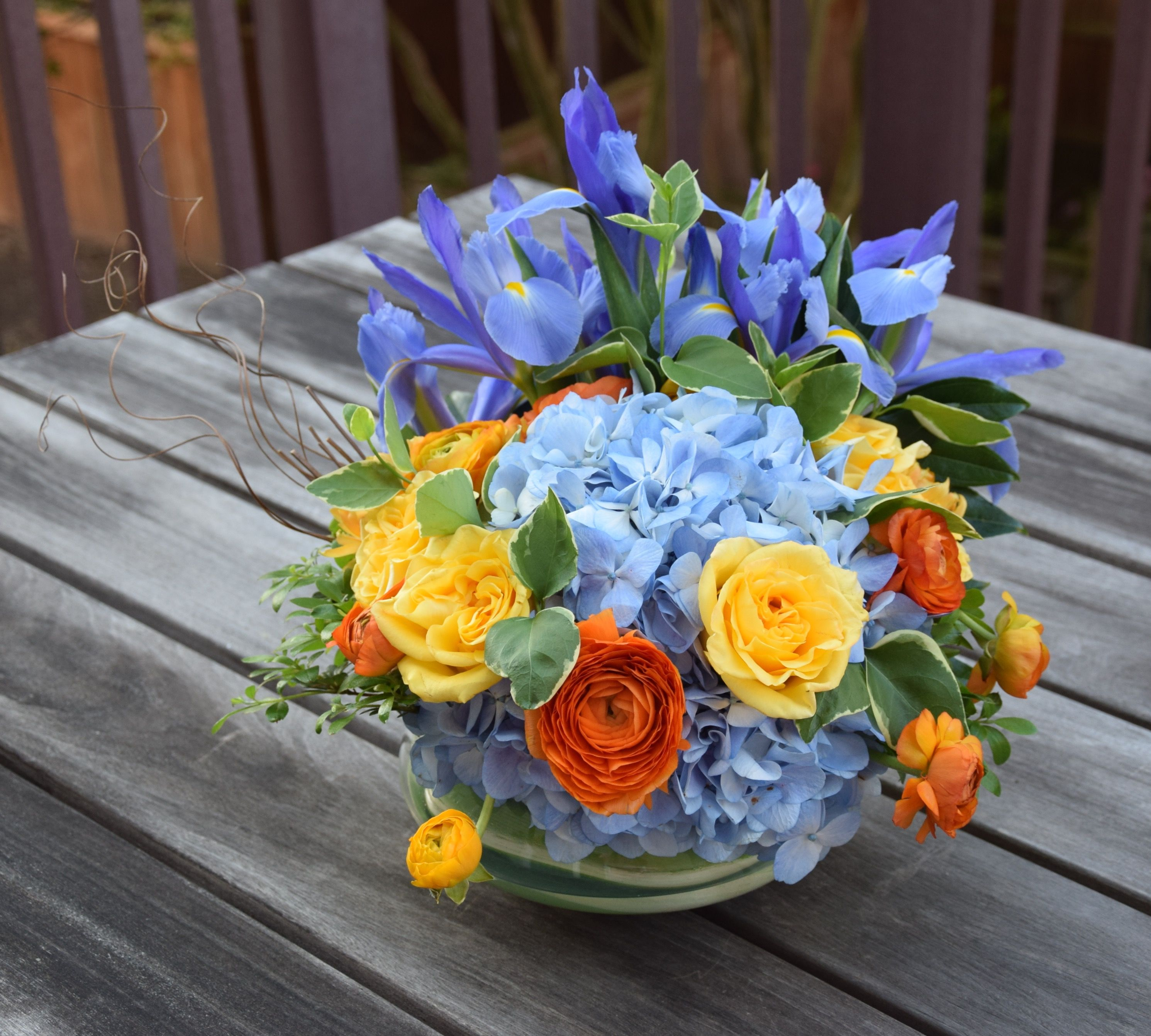 Flower Arrangement In A Bowl Blue Hydrangeas Yellow Roses Orange Ranunculus Blue Ir Rose Flower Arrangements Fresh Flowers Arrangements Yellow Rose Flower