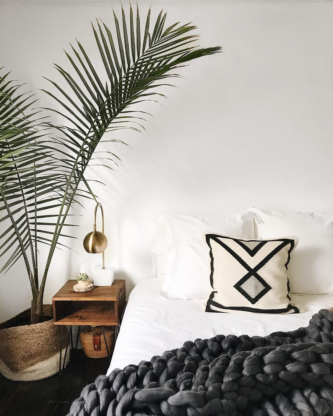 large plant, white walls, gold lamp, white sheets, large knit grey