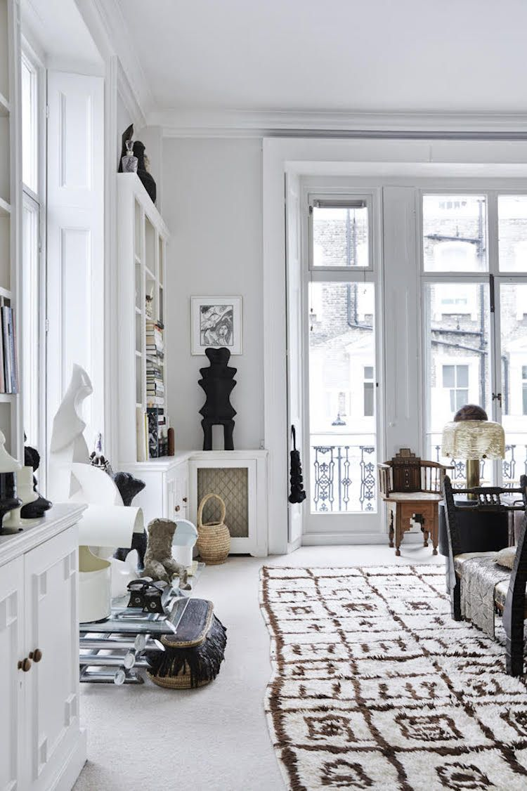 The living room features many storage shelves, printed rugs, modern ...