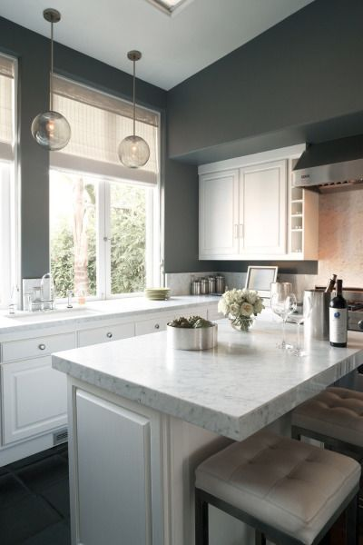 White kitchen cabinets, gray walls, black appliances and ...