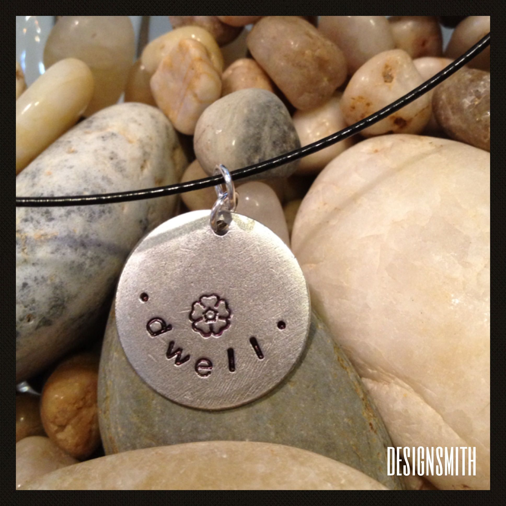 "Hand-stamped ""dwell"" flower pendant on black cording. $25 from designsmith."