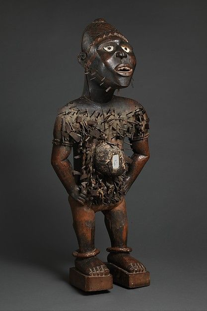 Kongo peoples; Yombe group 19th century Medium: Wood, iron, resin, mirrored glass, ceramic, plant fiber, textile, pigment Dimensions: H. 115 cm, W. 44 cm, D.  28 cm