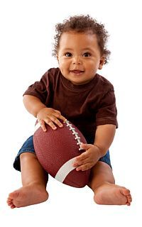 baby sitting and holding ball