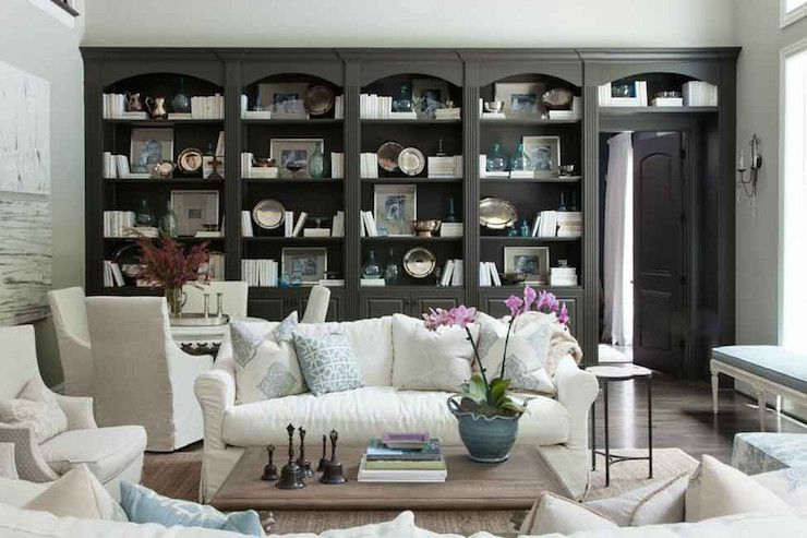 Beautiful Living Room Boasts A Wall Of Arched Black Built In Bookcases Stacked Over Black