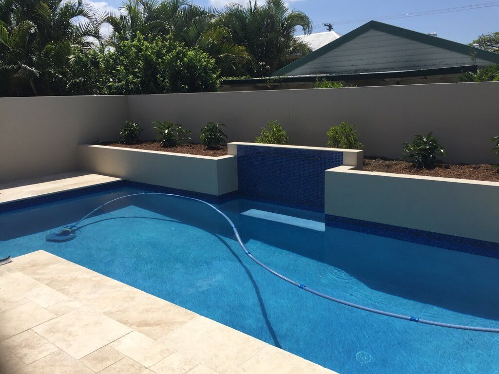 Swimming pool with water feature and rendered retaining for Pool design retaining wall