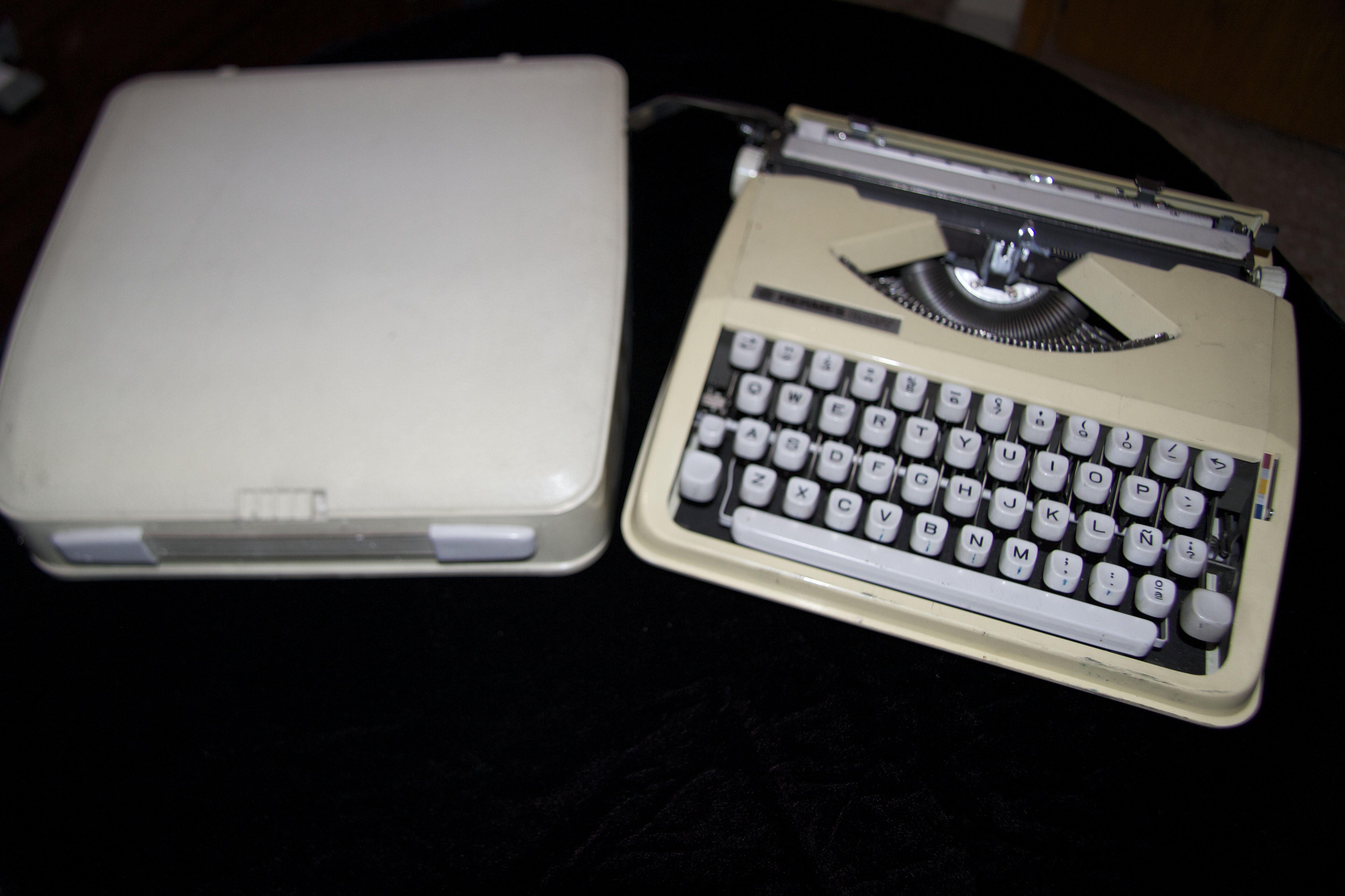 Máquina de escribir blanca con tapa.