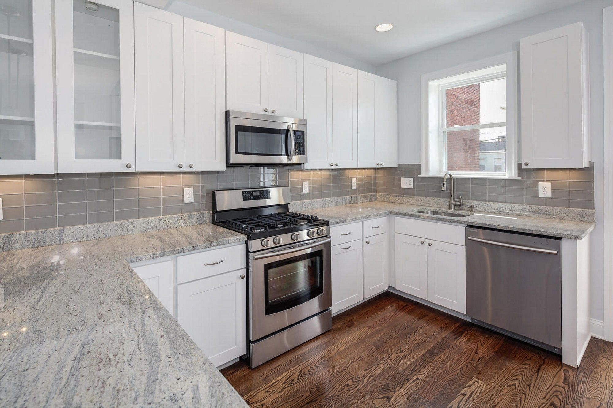Clean White Floating Cabinets Inside Open Kitchen With U Shaped Counter And White Spring Granite