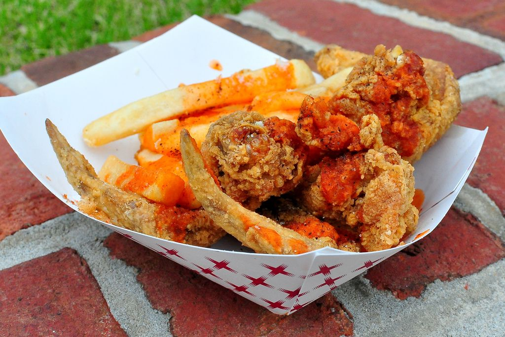 Basket of crispy fried chicken wings and French fries (topped with a tangy BBQ sauce.)