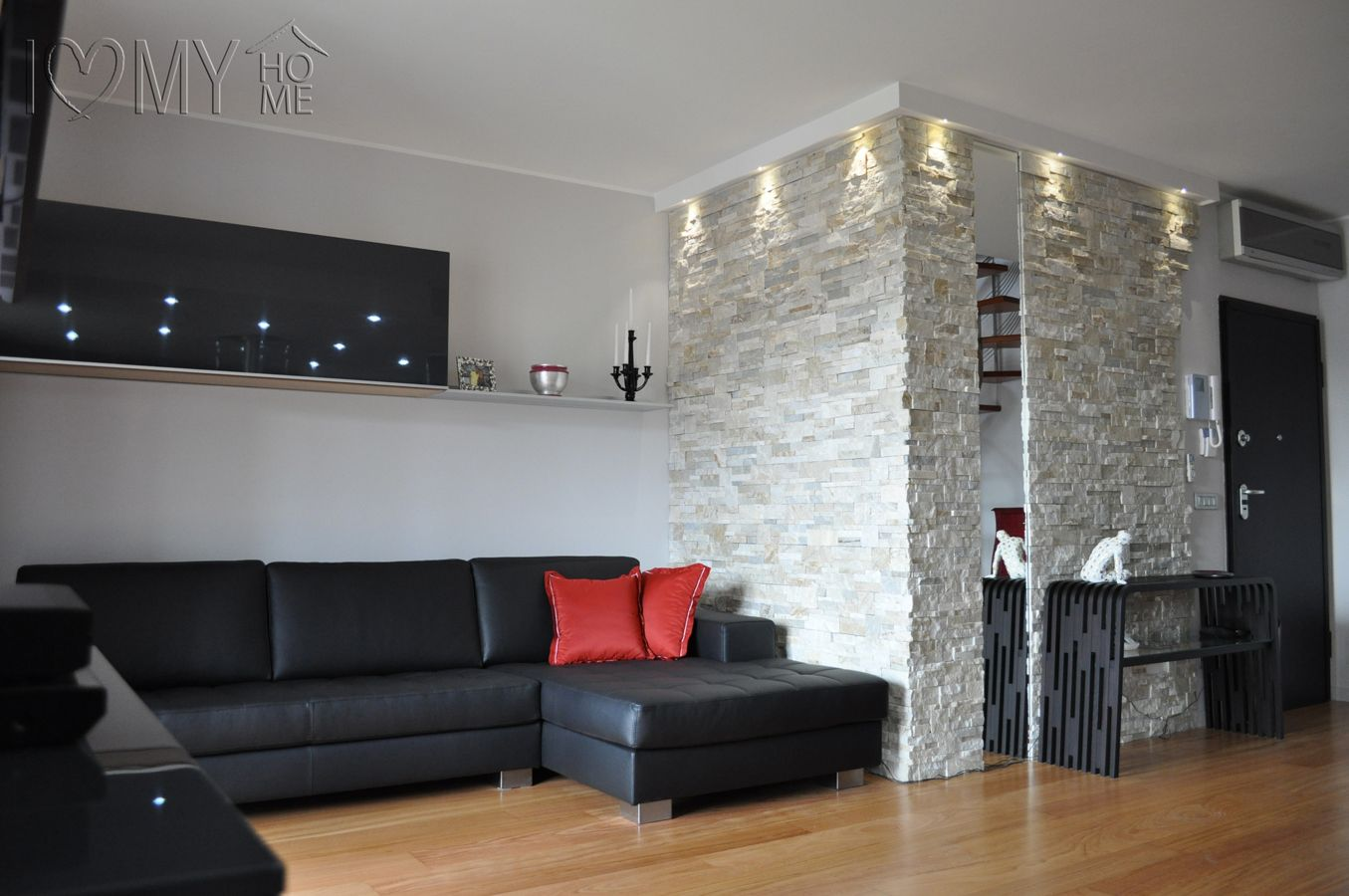 Openspace con parete in geopietra e specchio ed elegante