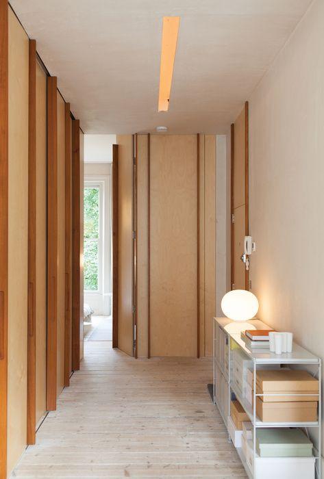 scandinavian style wooden corridor with wooden wall panels and full height floor to ceiling doors