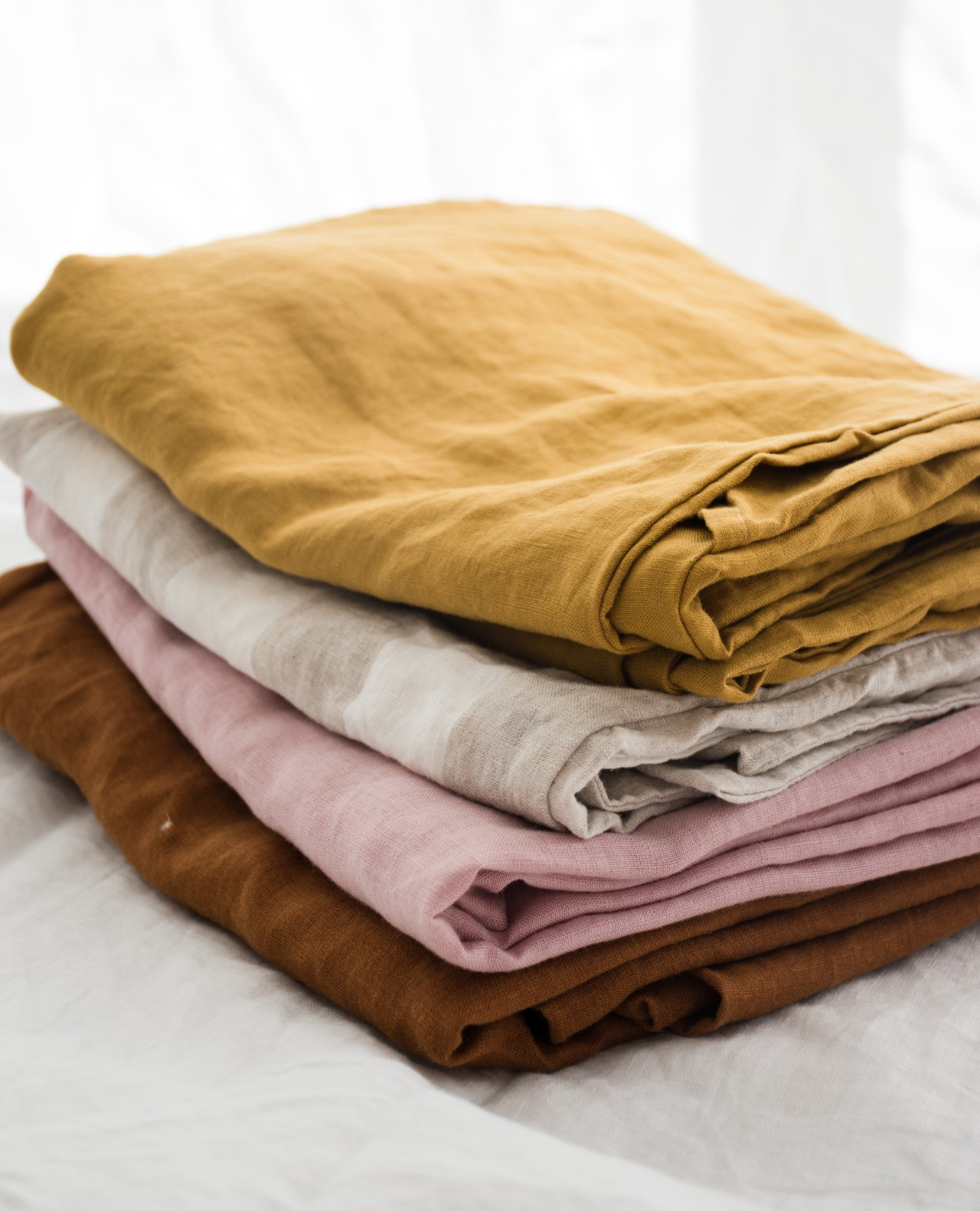 A French flax linen stack of Mustard, Thick Stripe, Wildflower Pink & Ochre. All of these colours can be mixed and matched and styled in your own personal heaven. Shope thee styles now.