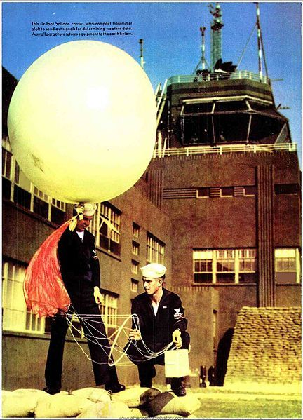 US sailors launching a radiosonde at a military airport in 1943. The radiosonde consists of a battery-powered instrument package (white box) carried aloft with a helium-filled weather balloon. As it ascends it measures temperature, humidity, and air pressure and radios the information to a ground receiver. At an altitude of around 70,000 ft the balloon pops, and the radiosonde floats back to earth suspended by the the red parachute visible on the support line. By WWII, the US Weather Bureau…