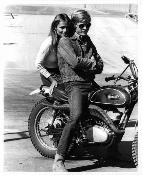 Lauren Hutton sitting on motor bike with Robert Redford