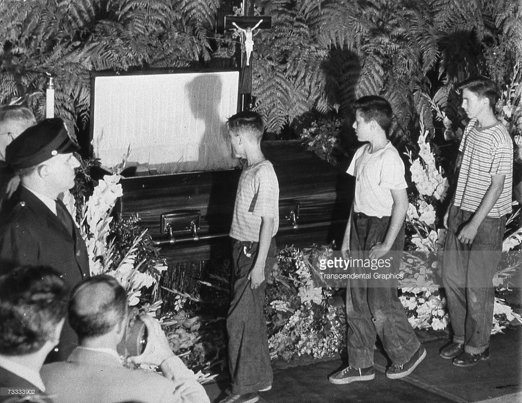 The body of Babe Ruth lies in an open casket in Yankee Stadium on August 17, 1948, as a crowd of young fans passes by.