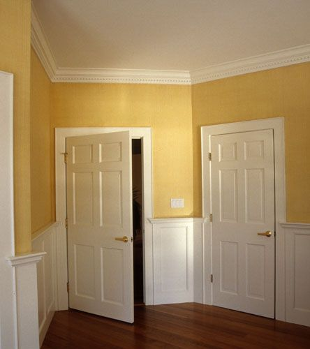 This hallway is trimmed with paneled wainscoting and crown molding ...