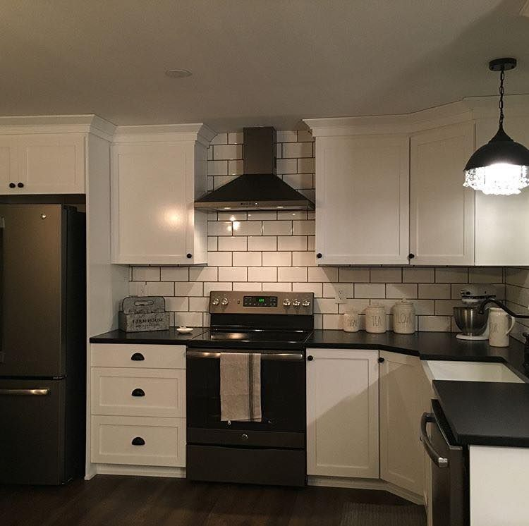 White Cabinets With Black Counters And White Subway Tile With Dark