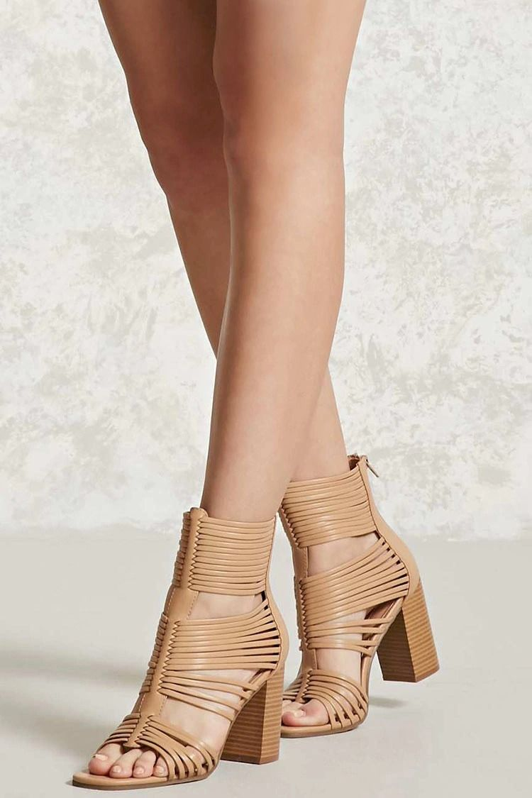 A pair of faux leather heels featuring a strappy design, an