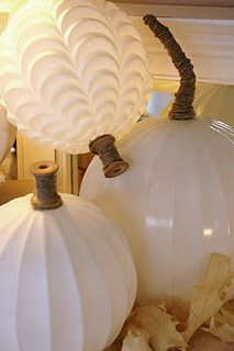 Decorating ideas for Halloween & Autumn: White glass pumpkins made from old light globes and vintage wood spools.