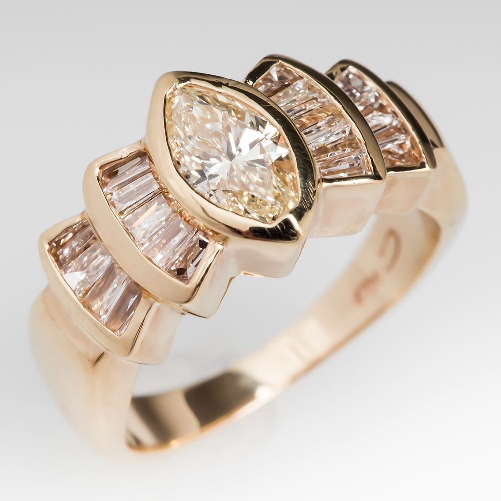 .87 carat natural diamond grading M / SI2. Each stepped shoulder has two fan elements that are channel set with lovely baguette cut diamond accents. The ring is crafted of solid 14k yellow gold