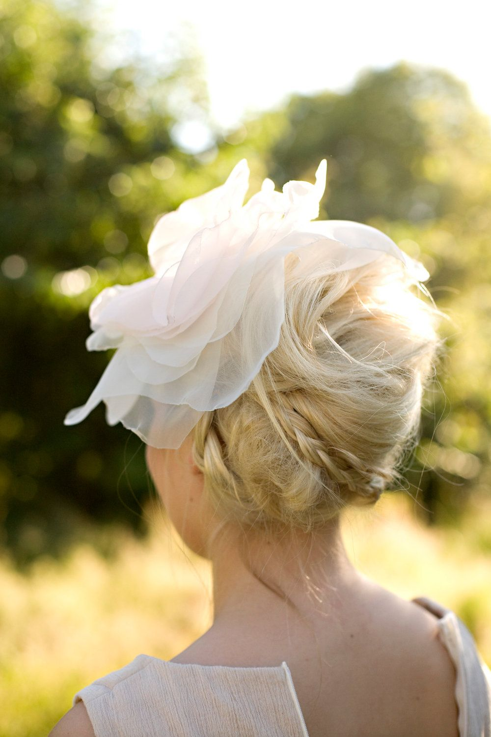 Soft French twist with a few braided pieces, topped off with an oversized hair flower. Swoon!