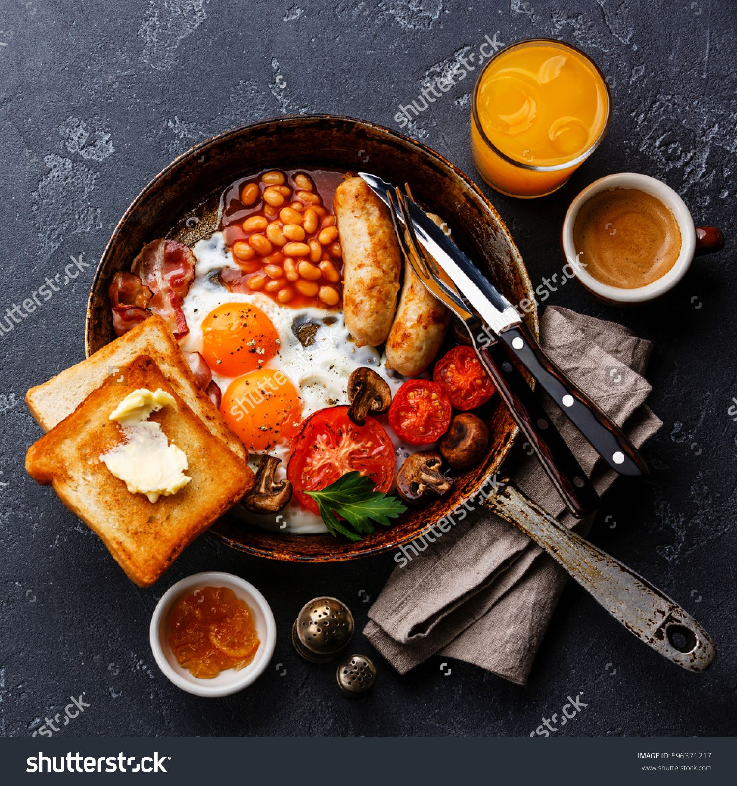 English Breakfast in cooking pan with fried eggs, sausages