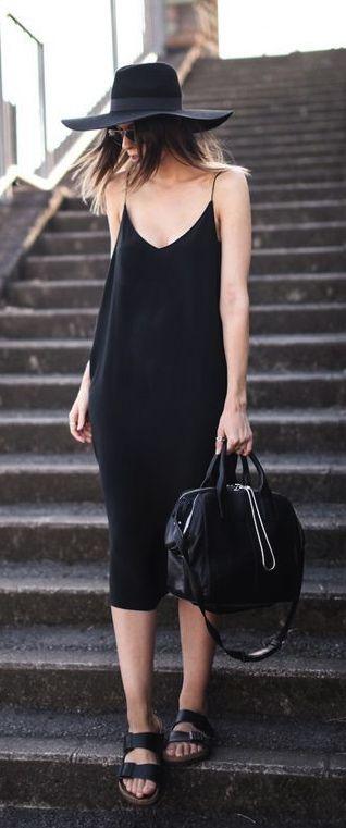 Black below-the-knee easy slip dress with a wide brim summer hat. Flat black Birkie sandals and big black bag. Sunnies. Elegant waif wandering the back streets. Style Planet
